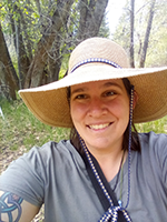 Photo of Heather smiling under a wide-brimmed gardening hat